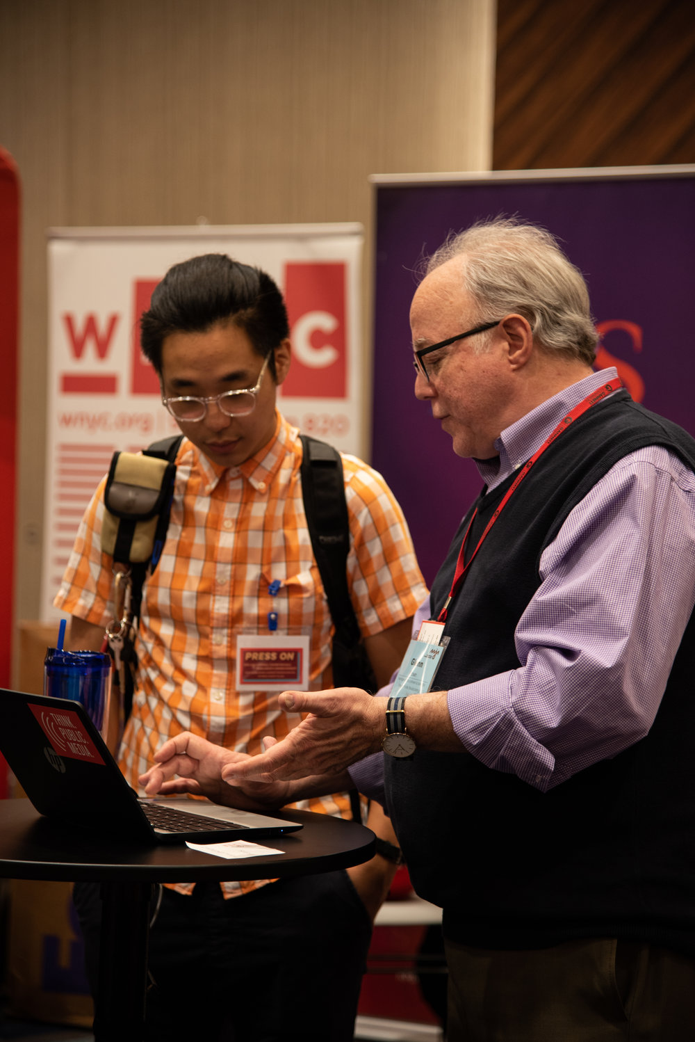 Glenn Brown, from Oregon Public Broadcasting, assists a conference attendee as they register on our website.