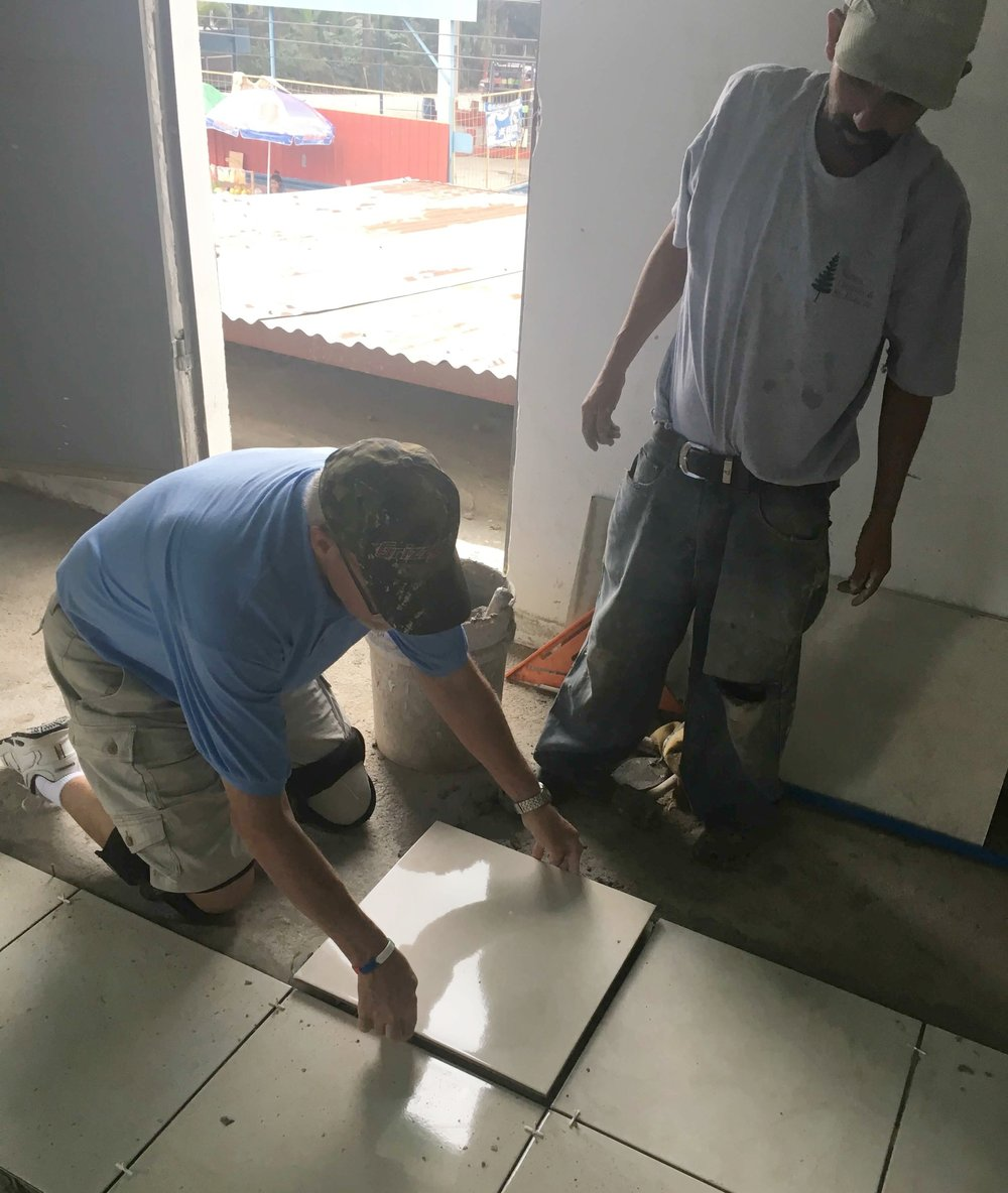 Dean Kucharski lays tile while a Guatemalan team member looks on.