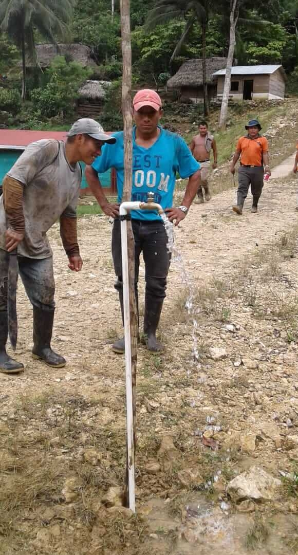 From the containers on the top of the hill, the water drops by gravity to the village of Sepoc. Here the workers turn on the faucet for the first time in their village!