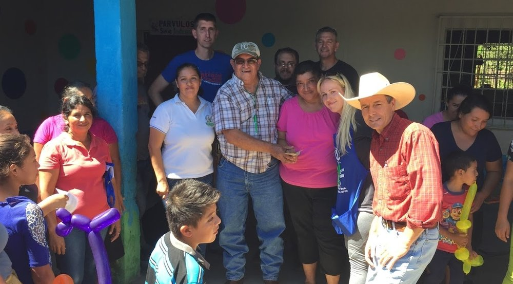 Cesar gives a gift on behalf of our group to a leader of a women's group near Quesada, Guatemala, to serve as seed money to buy materials for a micro business multiplication project that makes and sells lotion for women.