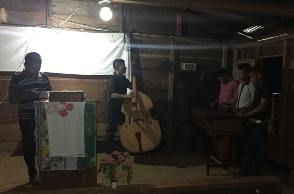 A Kekchi worship service begins in Ochul Choch. The song leader calls out the songs to the base fiddle player and the marimba team. Lights are provided by a gasoline powered generator that is rumbling outside.