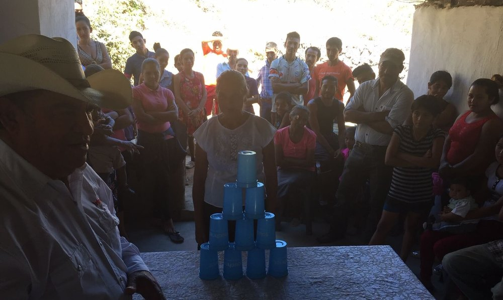 In a first group meeting near Quesada, Cesar explains the rules for a cup stacking game.