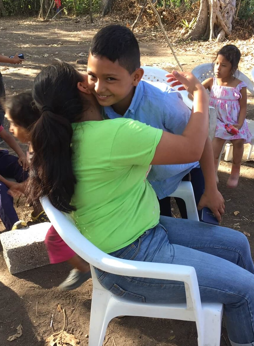 The group in Las Bolsitas started with a children's group. To reach more of the parents, Cesar offered a prize to each kid who ran home and got their mothers. This boy is thrilled that he got his mother and will soon get a prize!