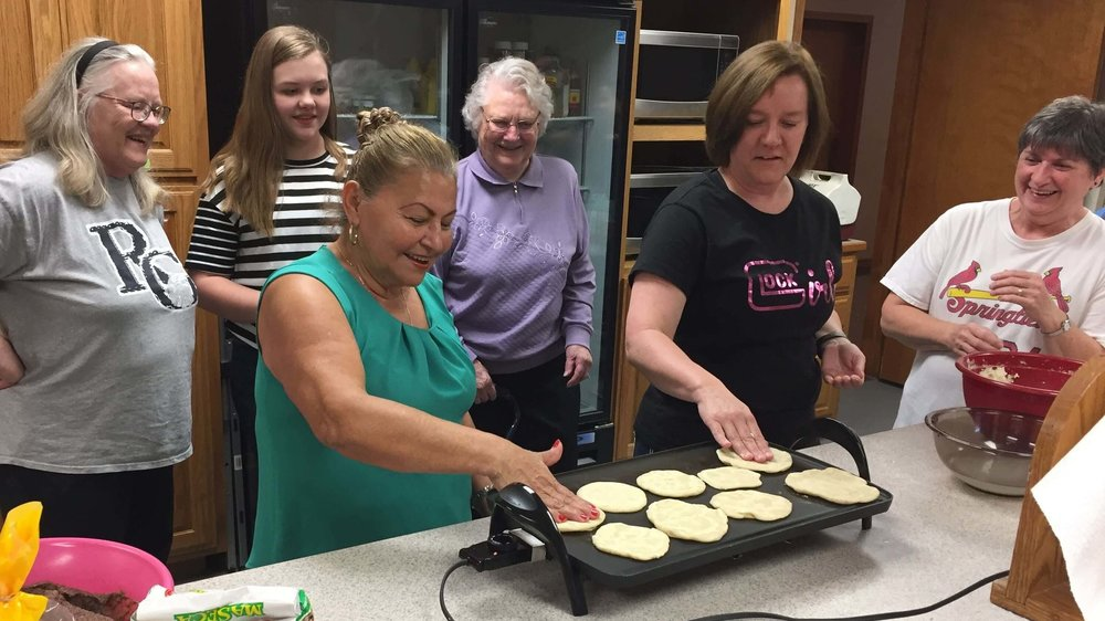With a group of friends at First Baptist of Avilla, Missouri, Elba shows how to flip the tortillas without a spatula! On the right, Joann Clark tries her hand at it.