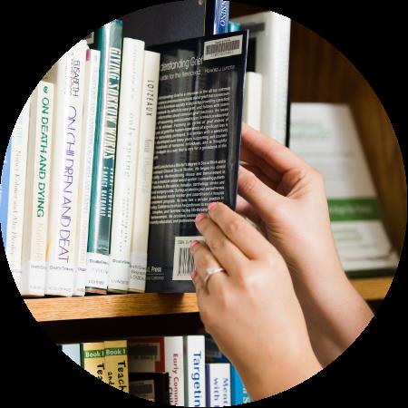 Hands grabbing book off bookshelf. Link to Resources.