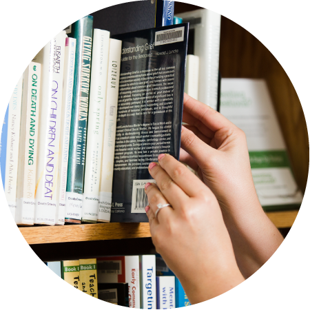 Hands grabbing book off bookshelf. Link to Resources.