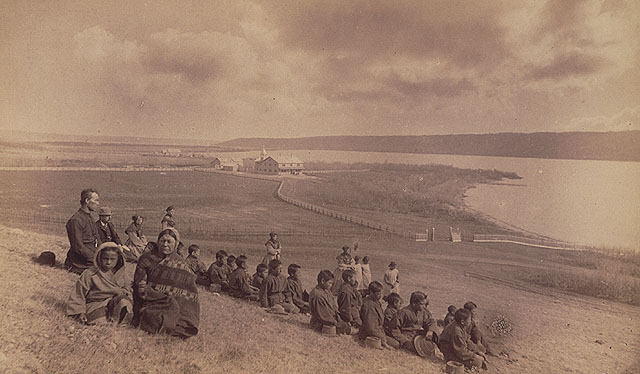 A06:   Fort Qu'Appelle Indian Residential School, students and family members sitting on a hill overlooking the school, Lebret, May 1885