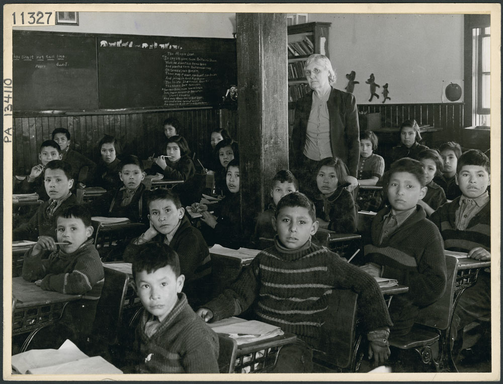 A12:   All Saints Indian Residential School, Cree students at their desks with their teacher in a classroom, Lac La Ronge, March 1945