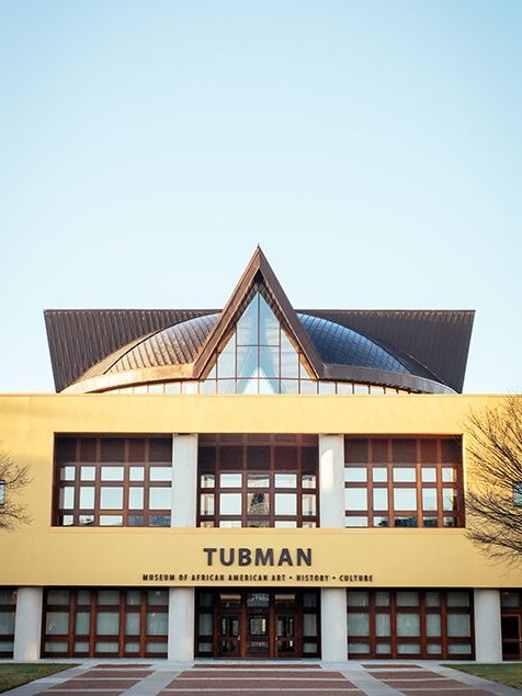 Tubman Museum of African American Art  ,  Matthew Smith, 2015    Completed in 2015, the Tubman Museum is a beautiful 49,000 square foot building featuring African American art, history and culture. The geometric symmetry of the structure is unmistakable and extraordinary. The pointed roof architecture looks as though it is piercing the crystal clear sky, creating significant contrast and negative space.