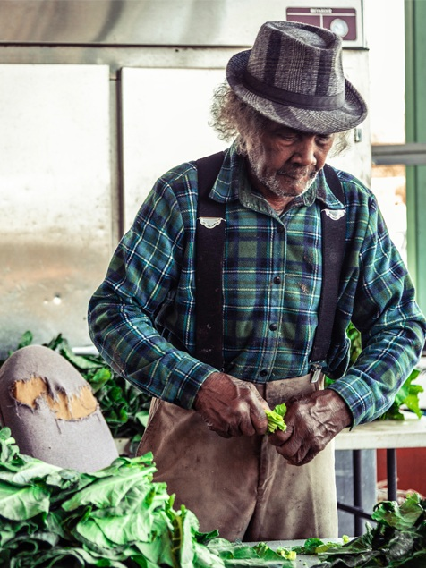 """Green Pickin' Marvin , Sydney A. Foster, 2019   """"Marvin Jones has been picking greens all his life, at least that is what he told me. I was infatuated with how fast he was able to pick the greens of stem. He was a machine. Marvin said to me, 'Baby, you trying to turn me in and spy on me?' I looked up from behind my camera and he said, """"I'm just playing, take whatever pictures you need."""" I met Marvin while roaming around at the State Farmers Market in Macon, Georgia. He had 2 of his grand daughters with him."""" -S.A.F."""