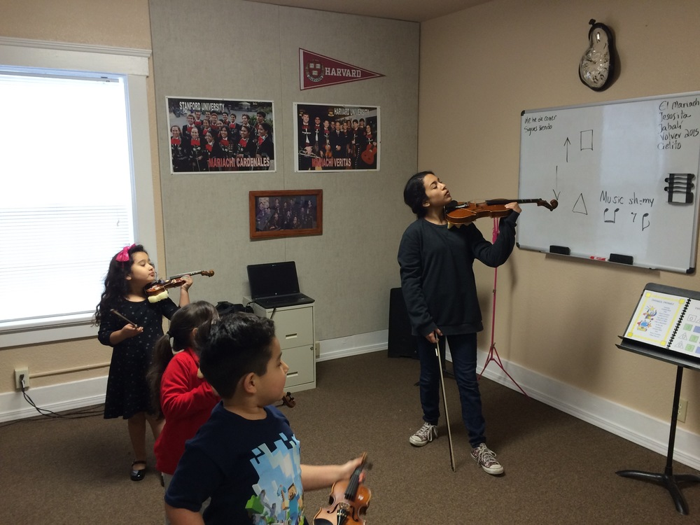 Instructor Anaí Morales showing youngsters how to properly hold the violin