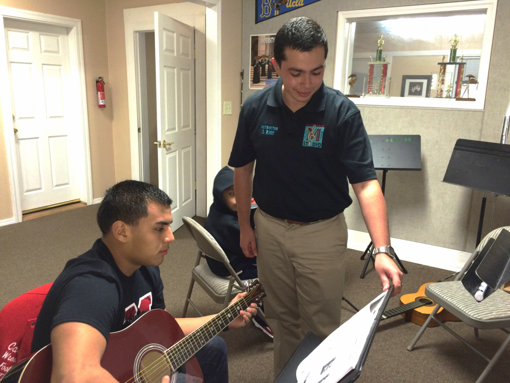 Instructor Sal Rios, a Music Education major at CSU Bakersfield, coaches a student at The Mariachi Studio.