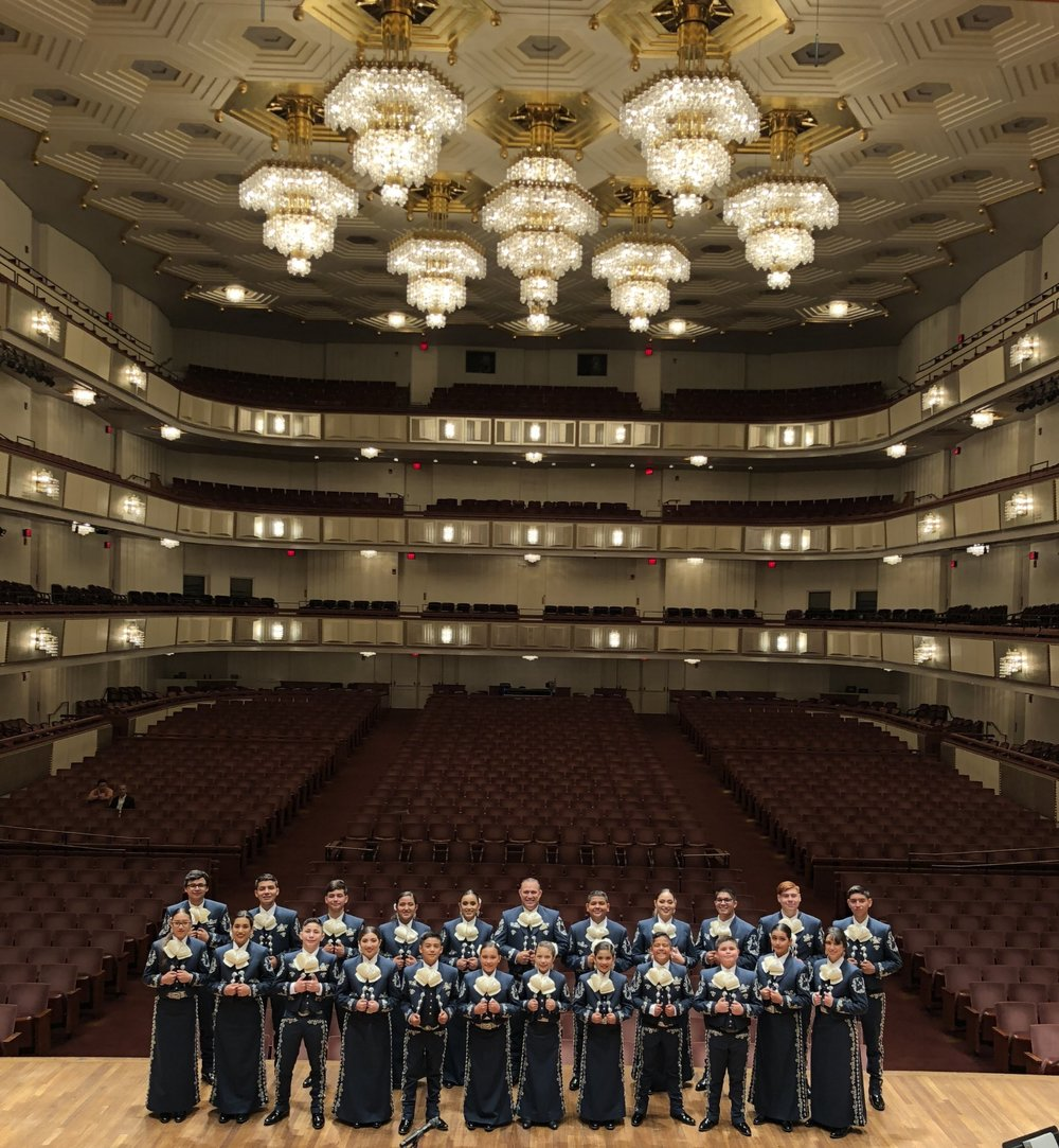Student Yari (front/center/right  ), posing with Mariachi Mestizo on the stage of Kennedy Center (Washington DC) before their debut concert.