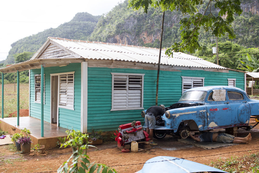 Two men working on a classic car in Viñales