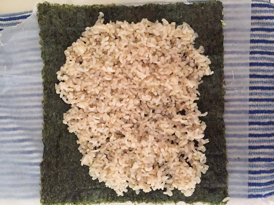 STEP 1: Lay towel out & cover with sheet of wax paper. Place Nori Sheet rough side up and shiny side down on top of the towel. Cover with as much brown rice as you desire.