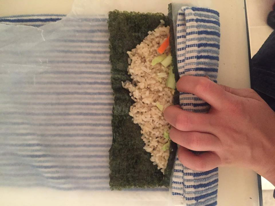 STEP 3: Line the towel, wax paper, and Nori sheet up and using the towel begin to roll everything together and push down tightly.