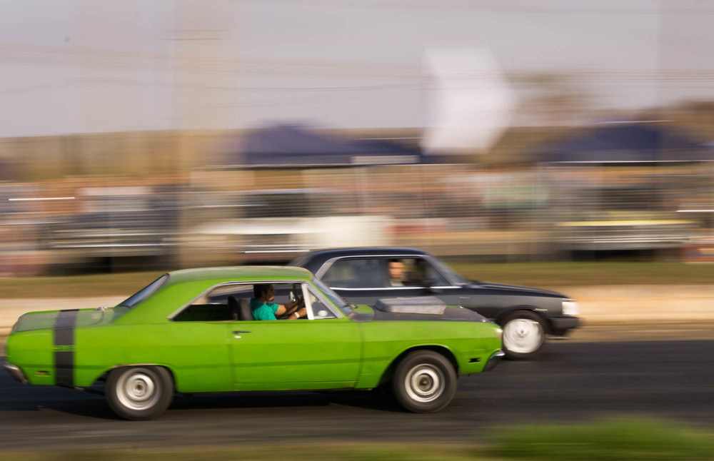 Green and Black car racing down track