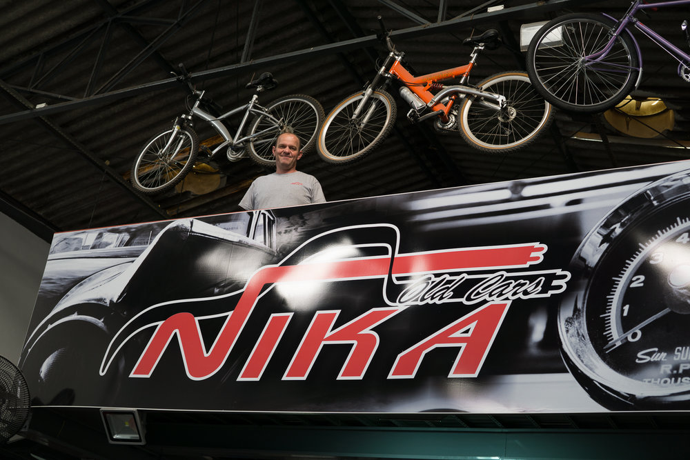 Nika in front of a banner with his shop name