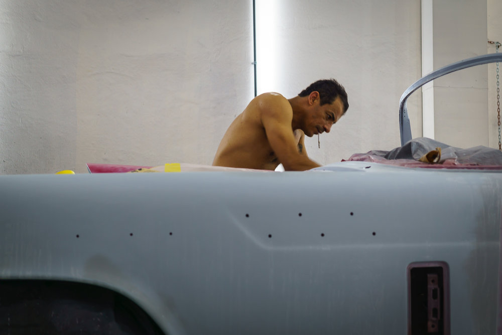 A worker sanding the paint of a car