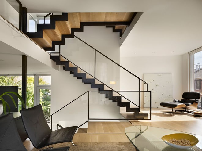 The contrasting metal used as edging on these timber stairs adds real punch. The repeating shape allows the eye to flow smoothly down the staircase to the each floor. The furniture perfectly complements the dark color.
