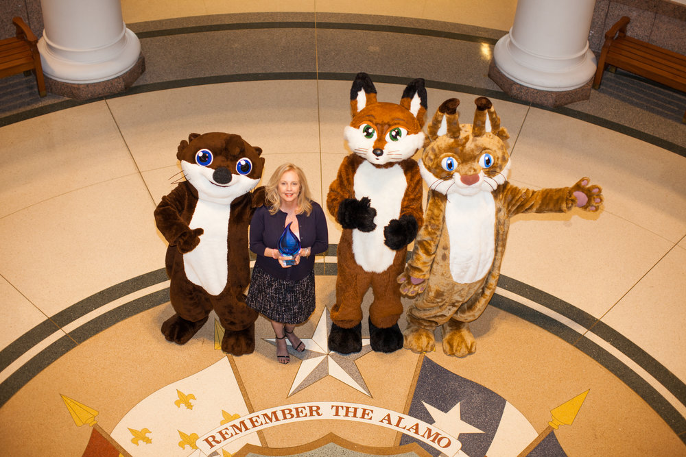 """Water4Otter characters and the program client at the Texas Capitol after winning a """"Watermark Award."""""""