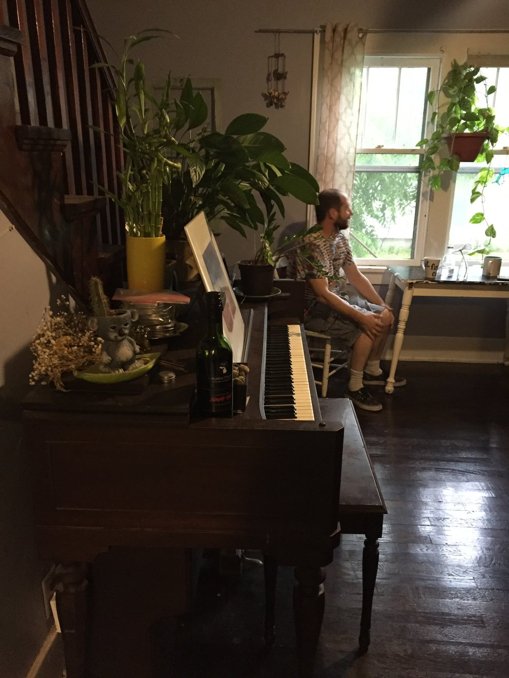 To the right of the piano is a small, but very cute, dining table.  She is killin' it with all the plants.  LOVE.