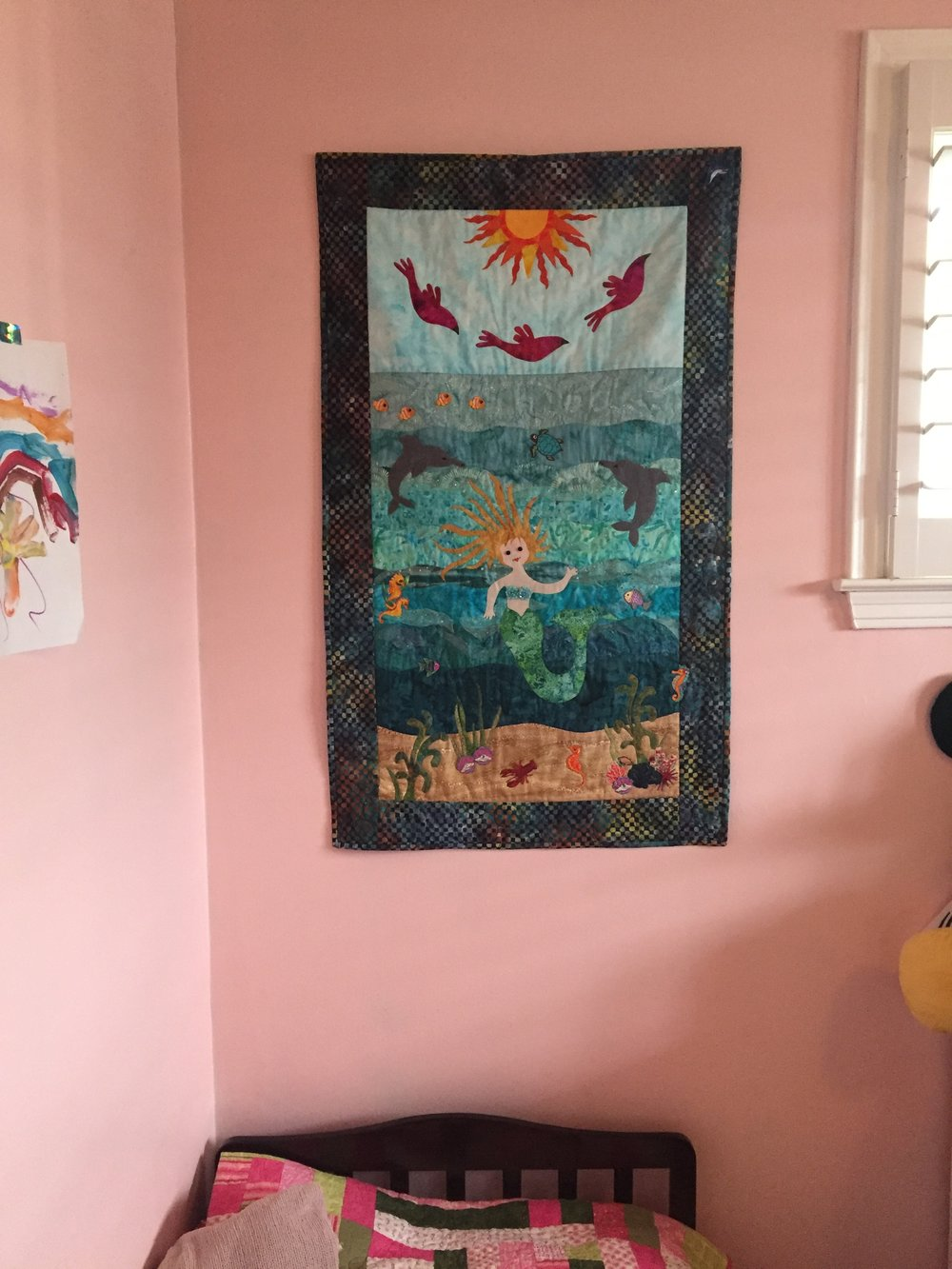 The mermaid wall hanging above the bed was made by my mother-in-law.  She is super talented with quilts.