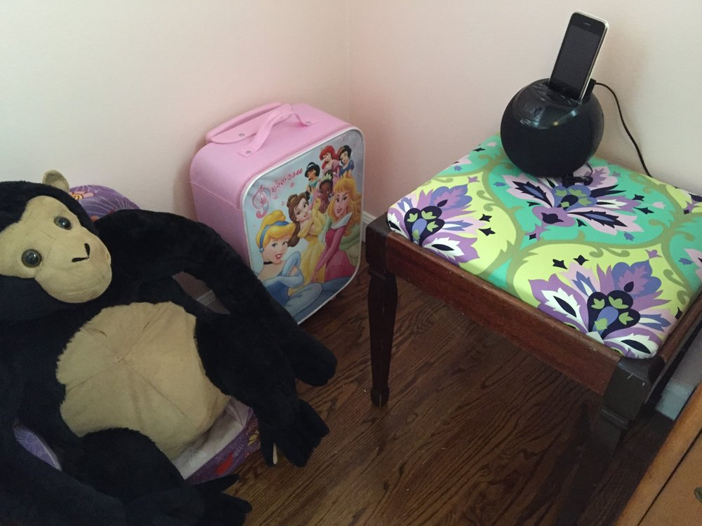 Next to the cubby shelf in this corner of the room is her squishy chair being used by her pet gorilla, her princess suitcase full of dolls, and a little stool that I recovered in a fun fabric. Stool/Bench: Garage sale; Suitcase: From my SIL