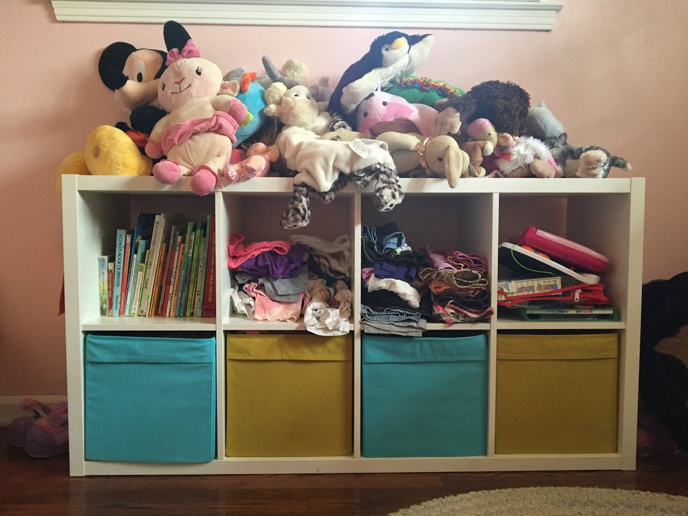 Books, clothes (they look like a big mess, but they're actually organized for Meena, so she knows where everything is) in the middle two top cubbies, and toys in the last.  The bottom bins are more clothes organized for her.  I have everything separated out so that she can get her own clothes out easily and dress herself.  No dresser with heavy drawers that can fall out on her. Everything is perfect for her height.  And this shelf is perfect for throwing her zoo of stuffed animals up on.
