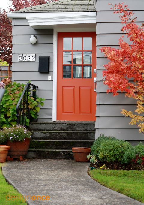 Image Credit:  DesignOnce    Gray siding, black mailbox, check. Orange coral door, check! Tree with color-coordinating leaves, check!