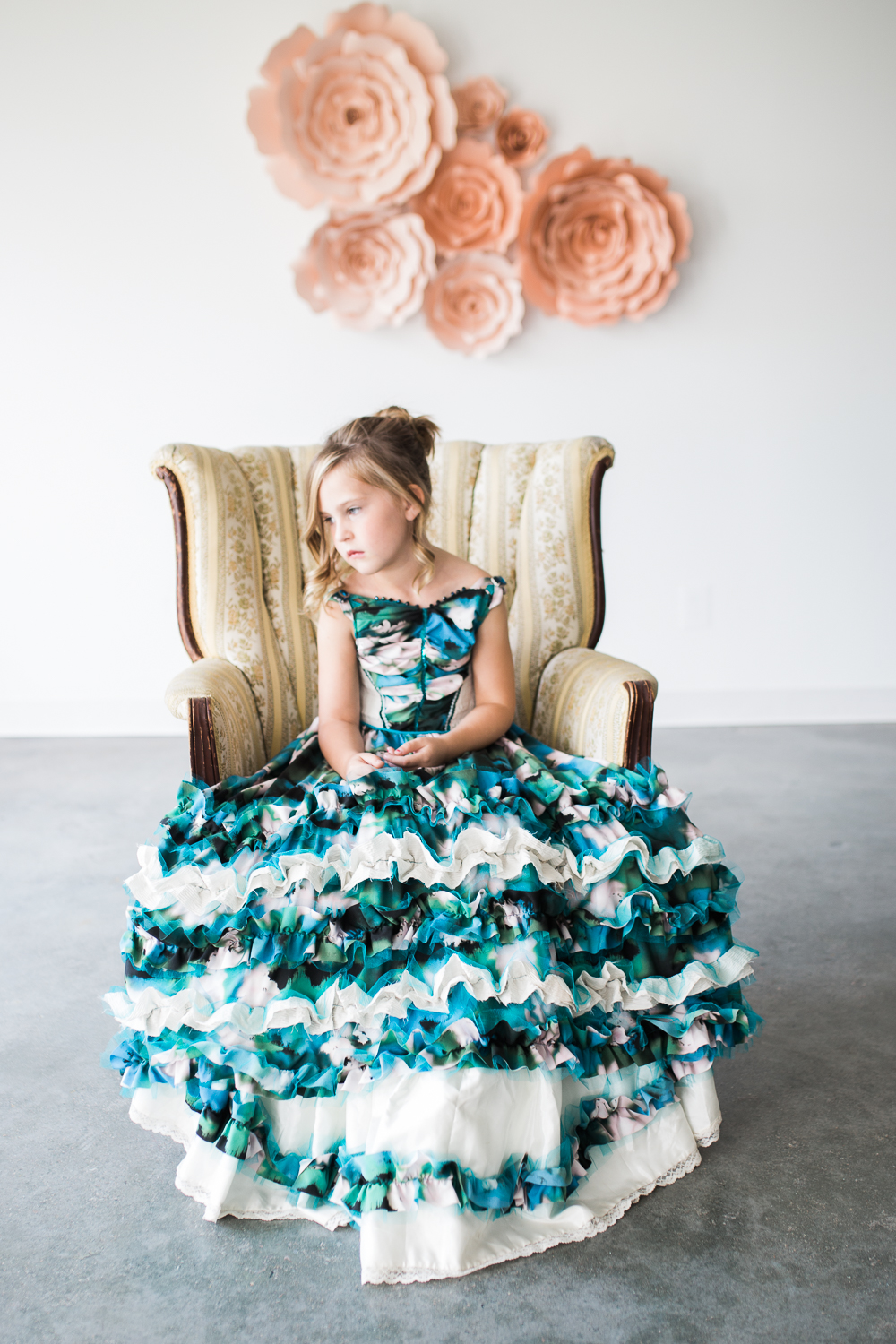 Indoor studio image of a little girl sitting in a vintage chair wearing a floor length silk gown.