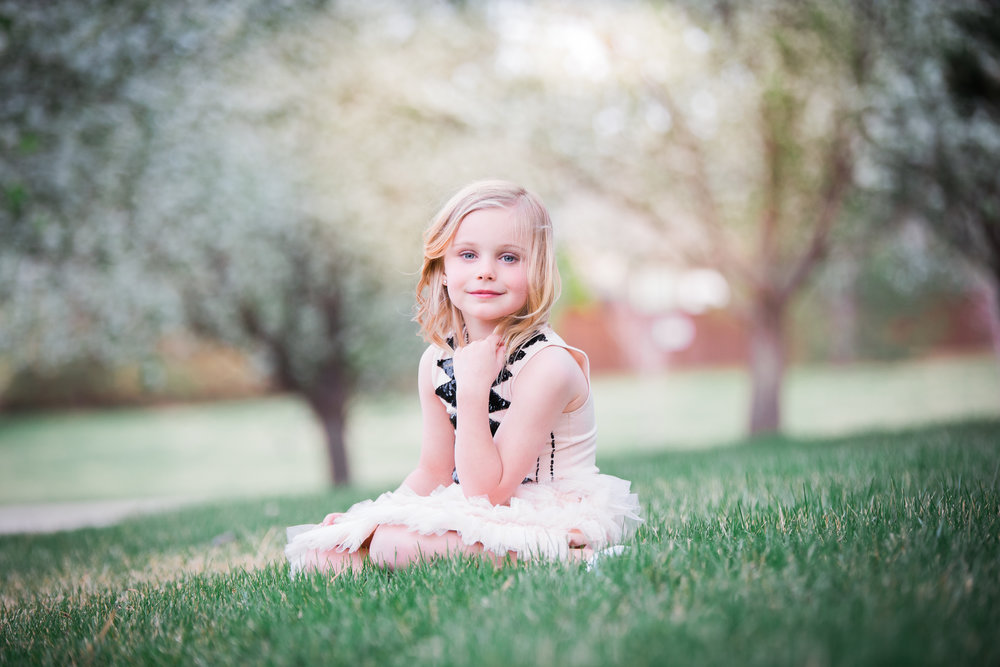A little girl sitting on green grass in a beautiful dress with the tree blossoms in the background.