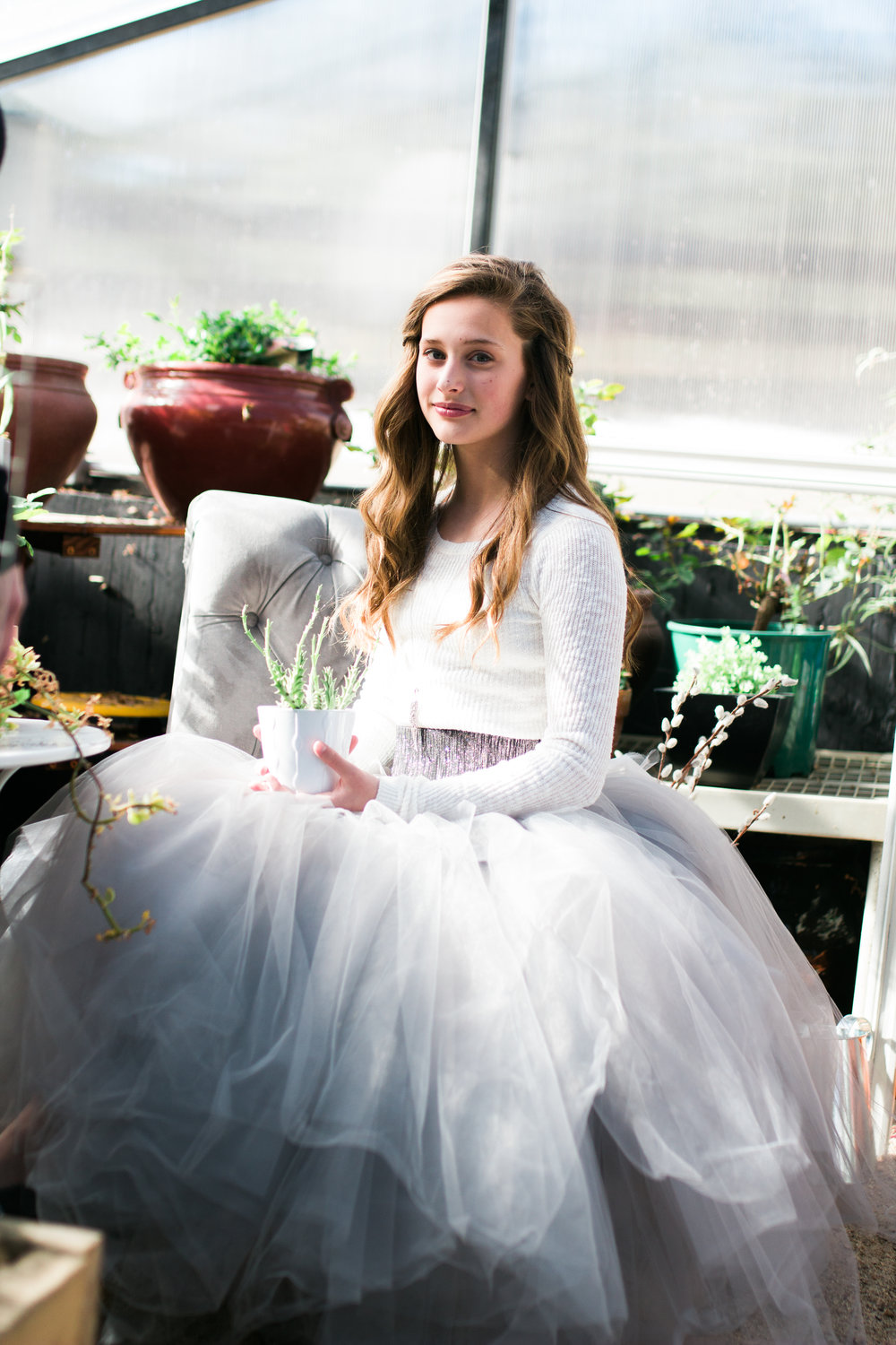 A teenage girl is sitting in a chair wearing a grey tulle skirt in a greenhouse.