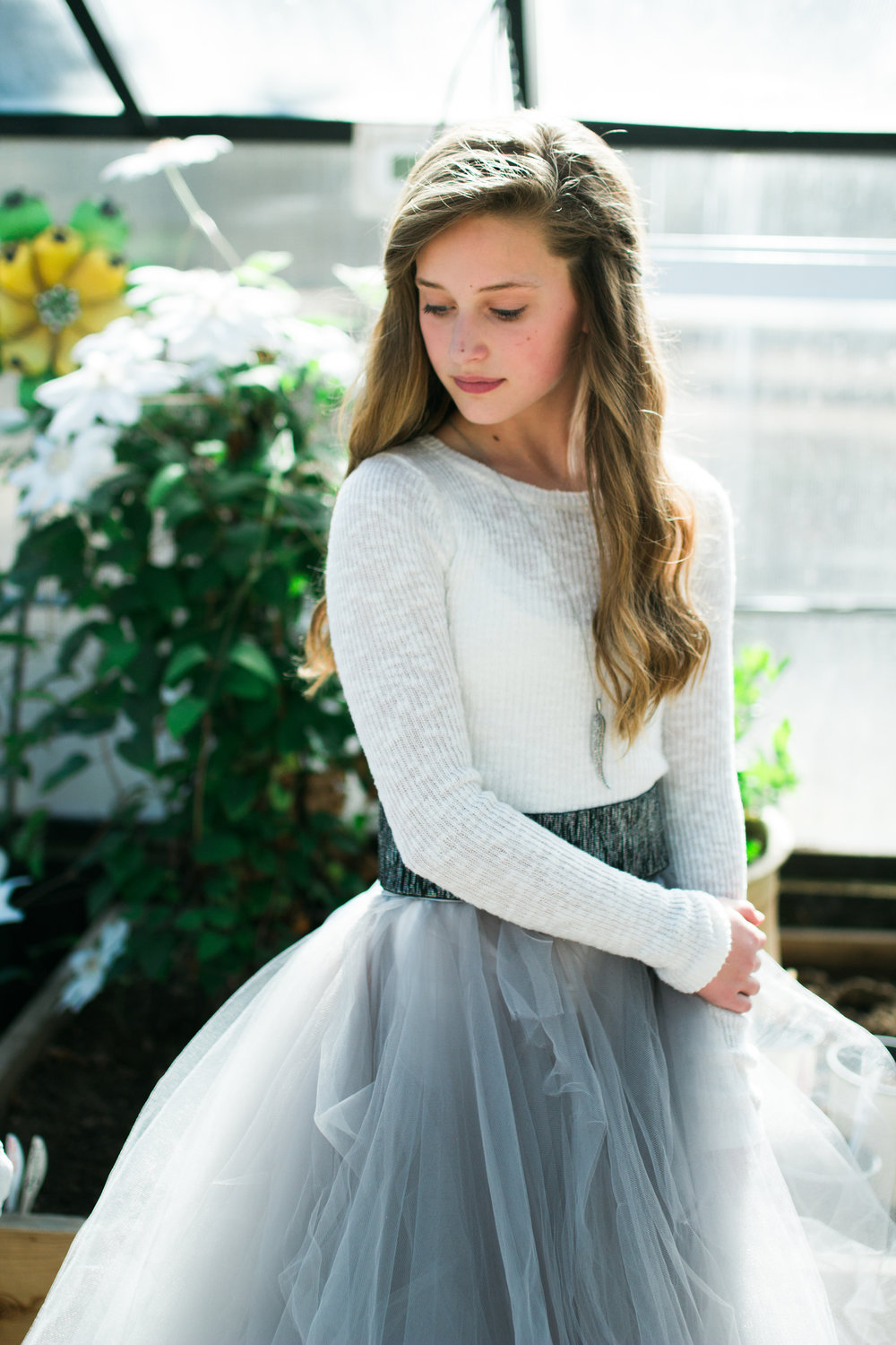 A young teenage girl looks down in a greenhouse while wearing a long and full tulle skirt.