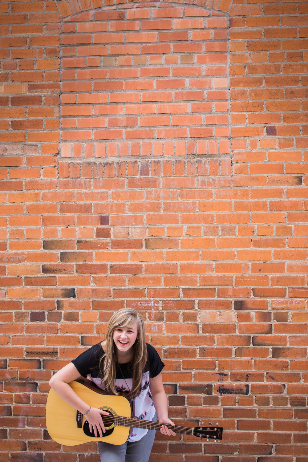 Teenage girl laughing with guitar standing in front of a red brick wall.