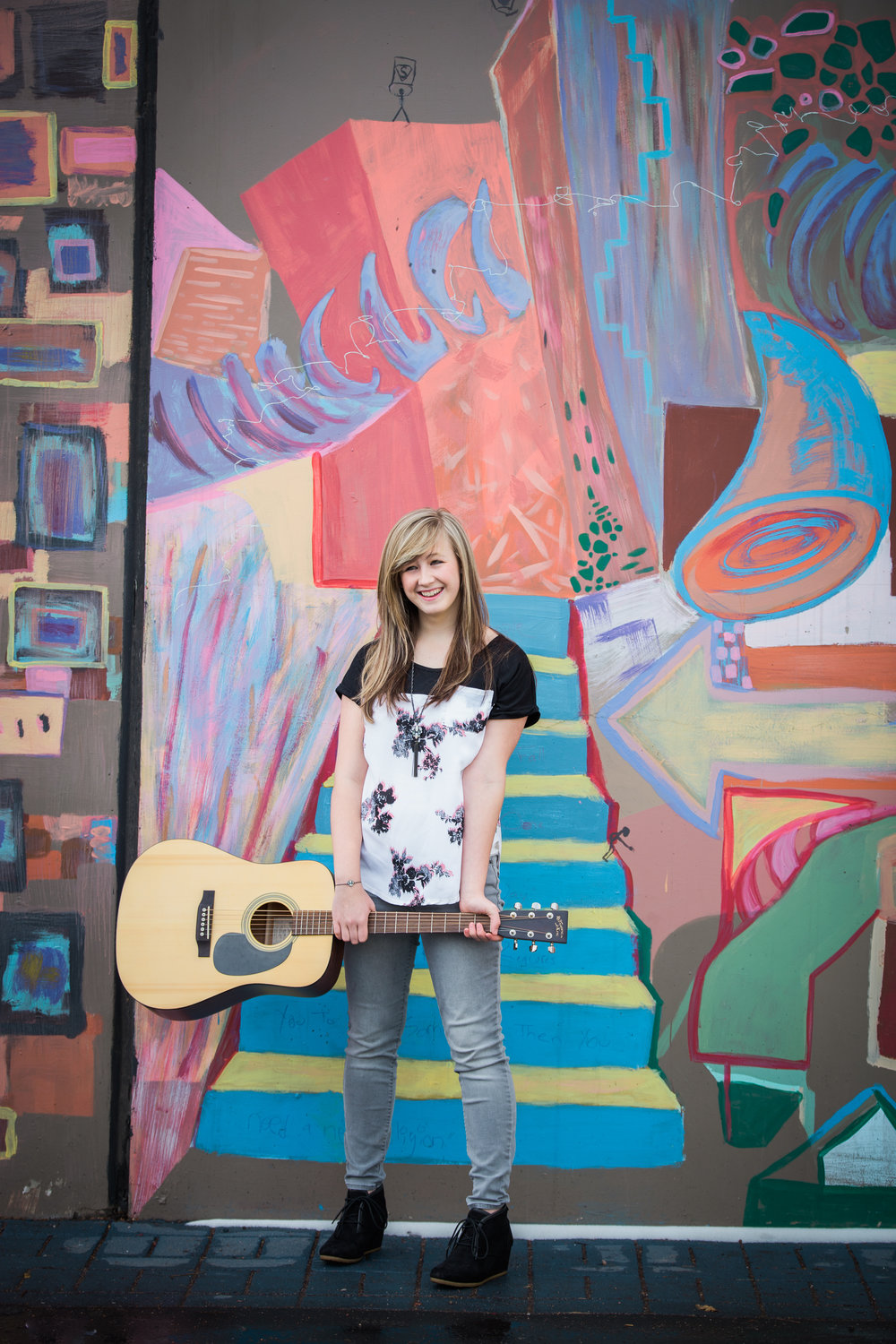 Teen girl holding her guitar standing in front of a graffiti wall in downtown Colorado Springs, Colorado.