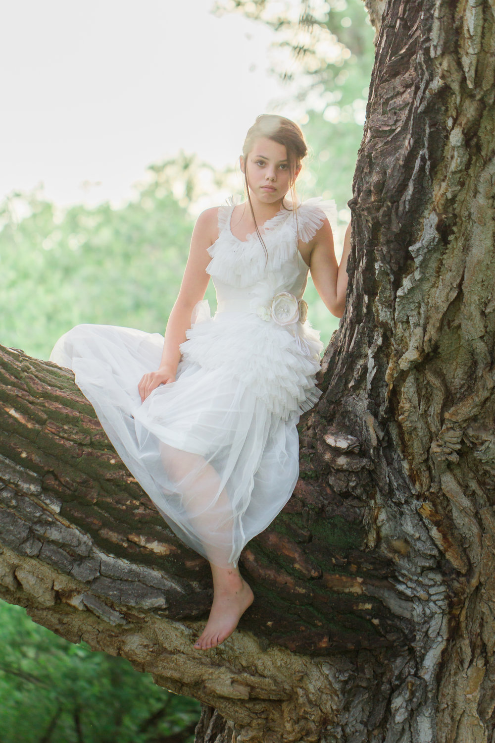 Teenager wearing a long white dress sitting in a tree.