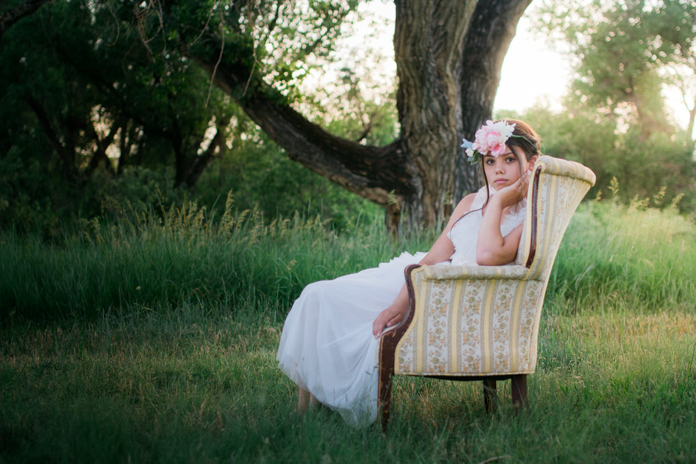 Teenage girl in long white dress and flower crown sitting in a vintage chair in Parker, Colorado.