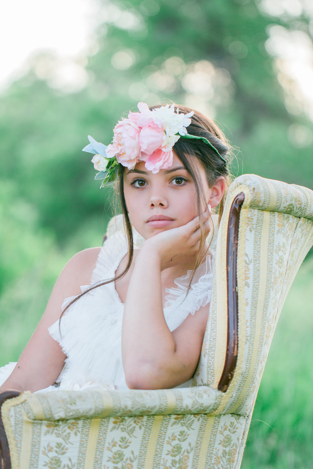teen girl wearing a flower crown sitting in a vintage chair with trees behind her.