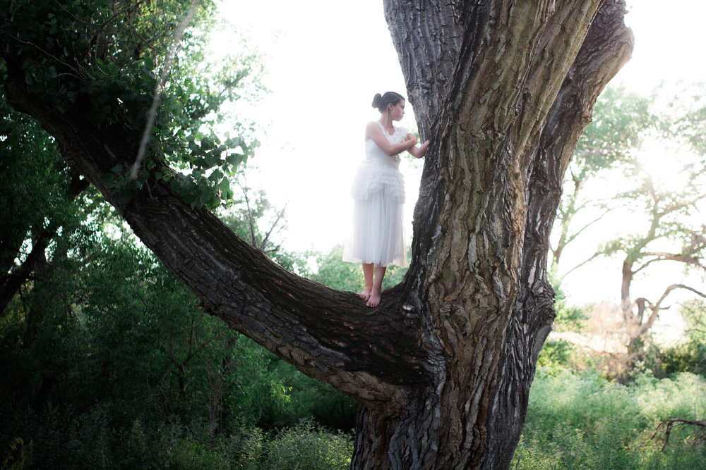 Teen girl wearing a long white dress standing on a large tree.
