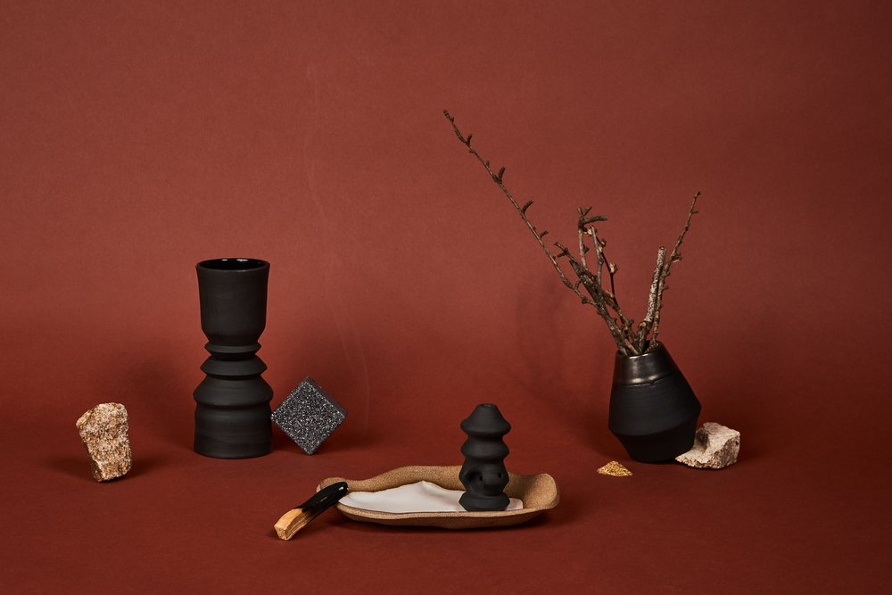 Left to right: two sculptural cups, handprint dish, sculptural pipe, small vase.