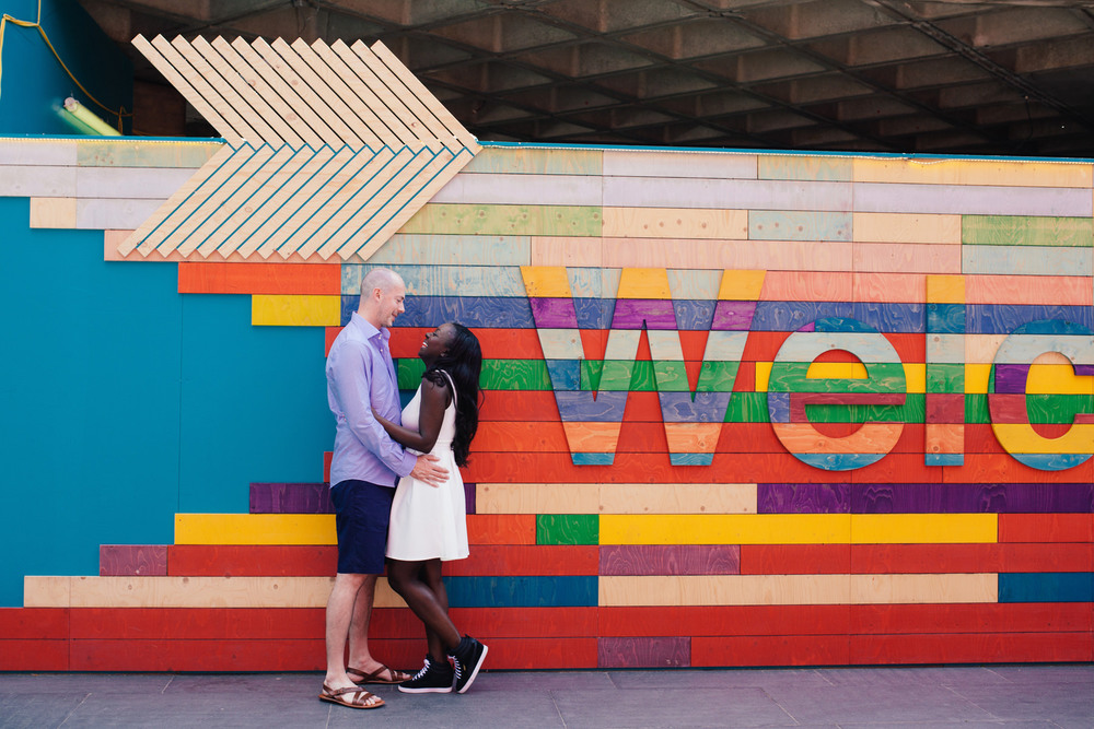 couple embracing against colourful Southbank background during pre-wedding shoot