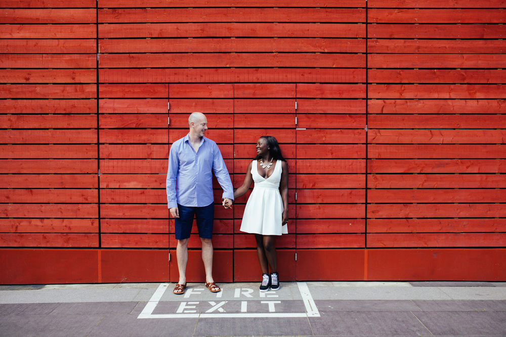 London-alternative-wedding-Southbank-engagement-photographer-couple-against-red-background