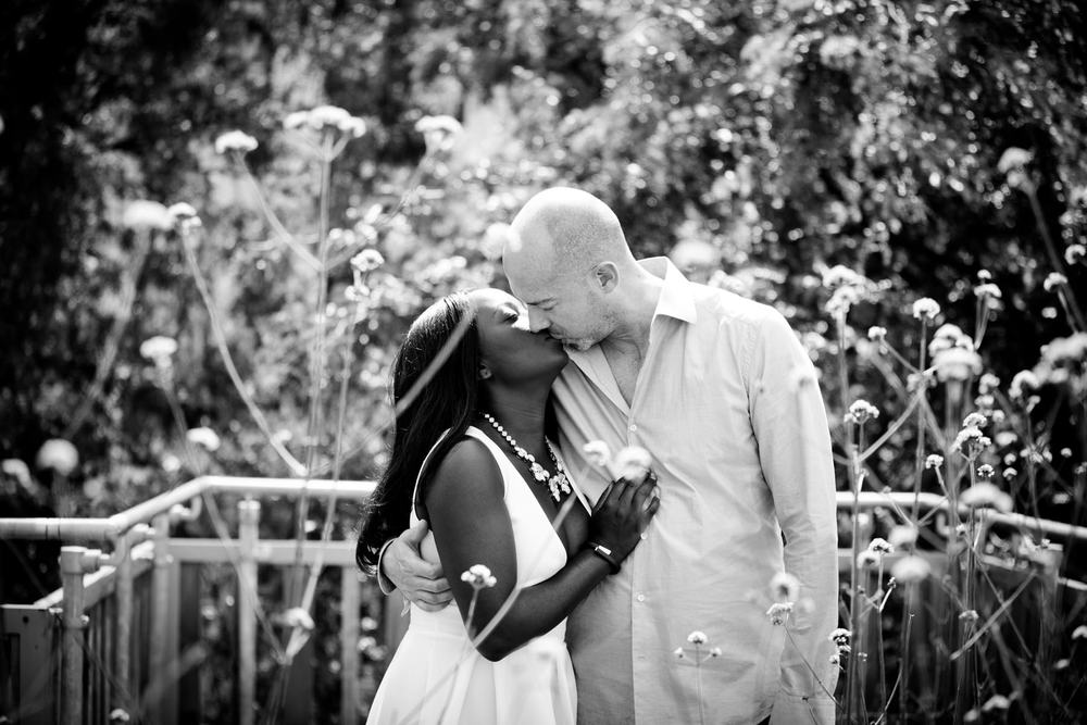 London-Southbank-engagement-photographer-couple-embracing-amongst-flowers-BW-engaged