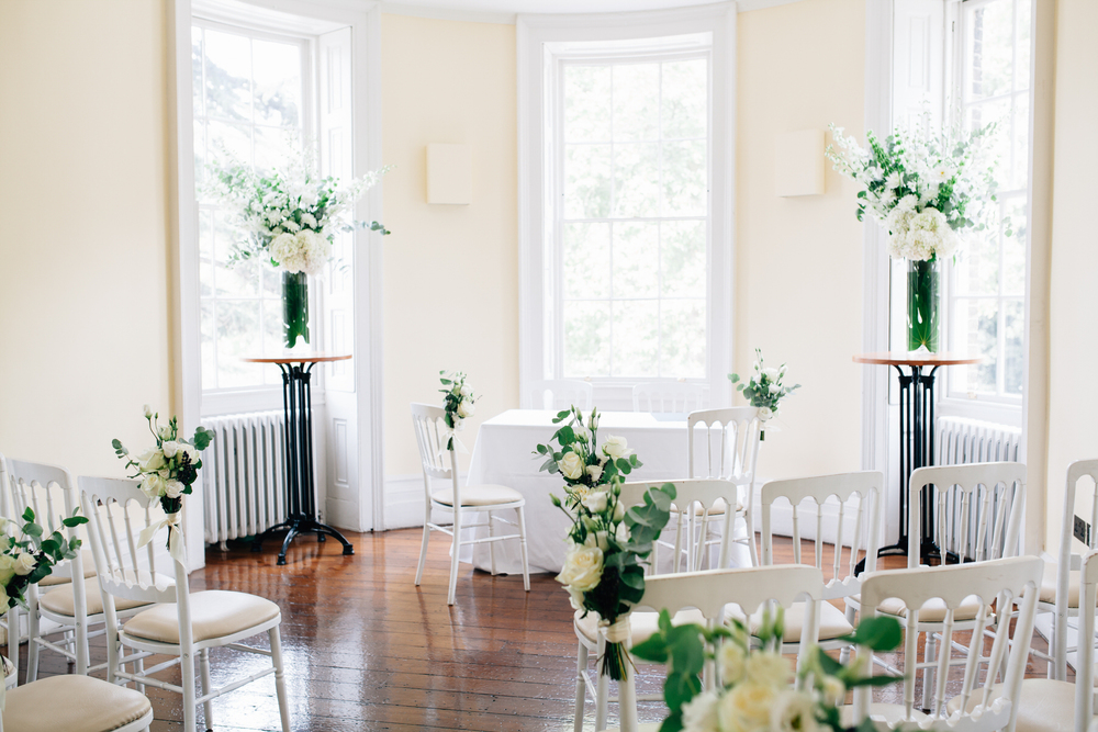 Clissold House ceremony room light airy filled with white roses hydrangeas