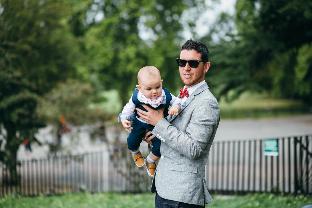 wedding guest holding his baby outside Clissold House