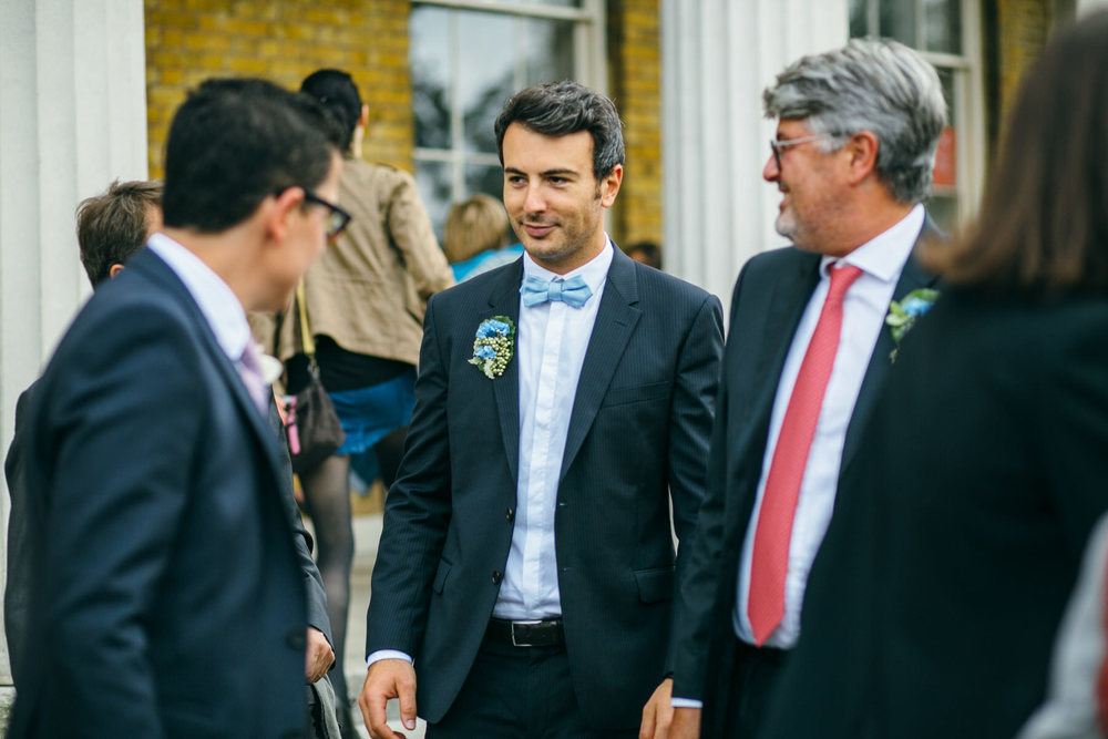 groom joking with guests outside Clissold House