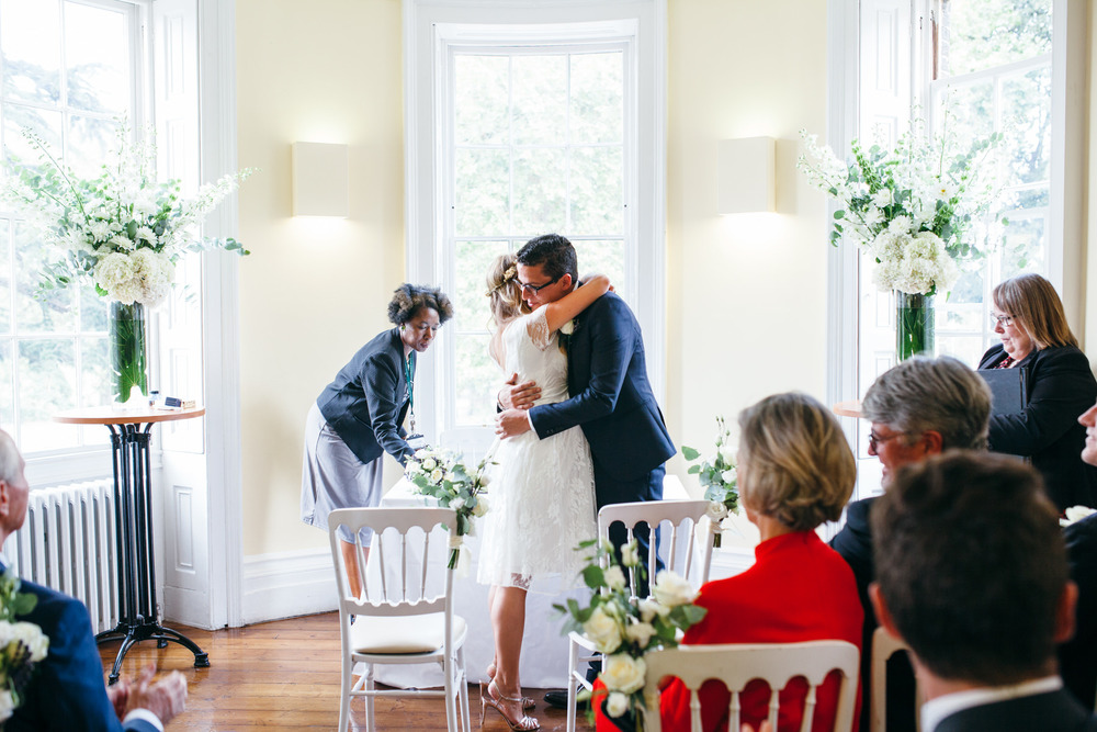 bride embracing groom Clissold House reportage wedding photographer
