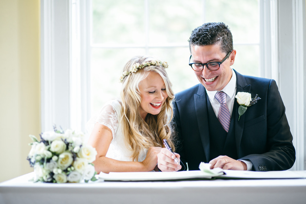 bride groom signing register Clissold House reportage wedding photographer