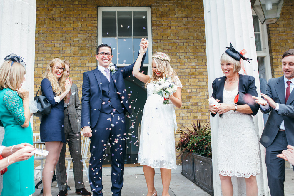 bride groom covered confetti on steps Clissold House